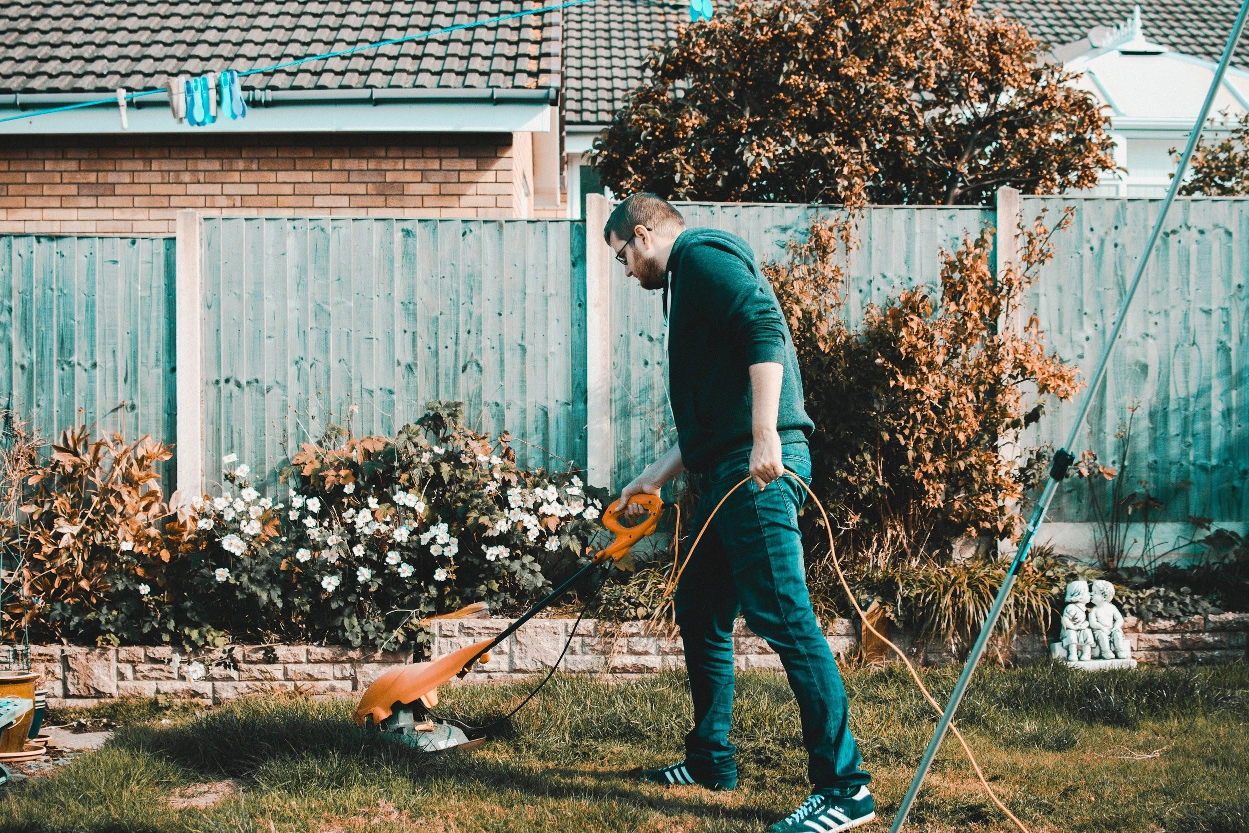 man mowing the lawn and gardening, one of the productive things to do at home